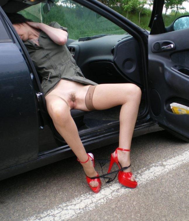 Mujer desnuda sentada en coche